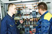 stock photo of electrical engineering  - two electricians builder engineers discussing electrical components equipment near fuseboard distribution box - JPG