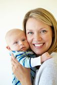 stock photo of cuddle  - Mother cuddling baby - JPG