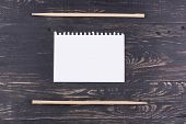 stock photo of chopsticks  - Chopsticks and a blank sheet of paper for recipes and menus on a dark wooden background - JPG