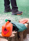 stock photo of chainsaw  - Orange plastic fuel canister with chainsaw on stumps - JPG