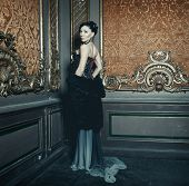 stock photo of edwardian  - Young beautiful brunette woman standing in the palace room - JPG