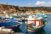 stock photo of gozo  - Port of Mgarr on the small island of Gozo Malta. Traditional maltese colorful painted fishing boat.