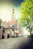 stock photo of cobblestone  - Small European town street with cobblestone pavement - JPG
