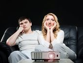 foto of watching movie  - Young couple watching movie or sport broadcast on tv sitting on sofa in living room - JPG