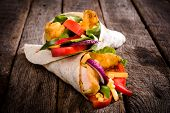 pic of sandwich wrap  - Tortilla wrap sandwich with fried chicken and vegetables on wooden backgroundselective focus - JPG
