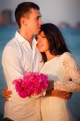 image of barefoot  - brunette bride and handsome groom barefoot stand at sand beach at dawn - JPG
