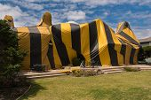 stock photo of tent  - Brown and yellow striped tent covers a house for fumigation process - JPG