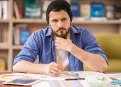stock photo of draft  - Serious man dressed casual sitting at the table and drawing draft at home office - JPG