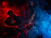 stock photo of guitarists  - Saxophonist beautiful young woman smoky stage and guitarist on background - JPG