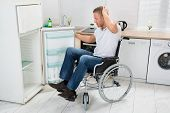 image of refrigerator  - Young Man On Wheelchair Looking In Empty Refrigerator - JPG