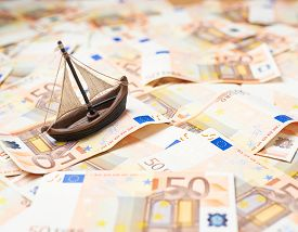 foto of fifties  - Tiny ship over the surface covered with the multiple fifty euro bank notes - JPG