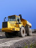 stock photo of oversize load  - portrait of dump truck on its path to worksite - JPG