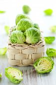 image of water cabbage  - Wet brussels sprouts in basket on the white wooden table - JPG