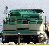 foto of pontoon boat  - A fishing pontoon boat docked at a pier all loaded and ready to go - JPG