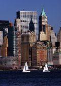 foto of sail-boats  - two sail boats sail along the skyline of new york city - JPG