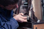Carpenter Restoring Wooden Furniture With Plaster And Putty Knife poster