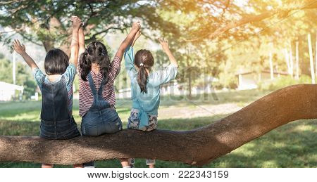 poster of Children friendship concept with happy girl kids in the park having fun sitting under tree shade playing together enjoying good memory and moment of student lifestyle with friends in school time day