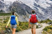 Hiking people walking on mountain trail trekking with backpacks. Hikers couple backpacking in nature poster