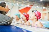 Row of three schoolkids in swimwear looking at their trainer out of water and listening to him poster