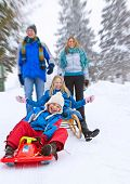 young funny family is sledging in winter-landscape