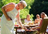 food, people and family time concept - senior man cooking meat on barbecue grill at summer garden bb poster