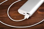 Battery Bank For Charging Mobile Devices. Silver Smart Phone Charger With Power Bank. External Batte poster