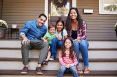 Portrait Of Family Sitting On Steps in Front Of House poster