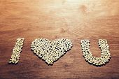 I love you symbol made out of little wooden hearts on a wooden background. Love concept. poster