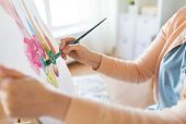 art, creativity and people concept - hands of artist with paint brush and easel painting still life  poster