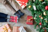 High angle view of loving couple feet near christmas tree with gifts. Top view of man and woman wear poster