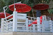 Open Veranda Of The Restaurant With Furniture And Red Umbrellas Behind A White Wooden Fence poster