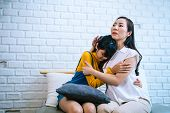 Asian Mother Comforting Crying Teenage Daughter In Miserable, Stressed, Depressed, Sad State Of Mind poster