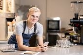 Happy young waiter with pen and smartphone standing by workplace in front of camera while working wi poster
