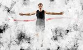 Runner wins by crossing the finish line.  Strong athletic man, running on white smoke background wea poster