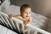 Top View. A Child Alone Stands At Home In A Crib Holding On To Her Side. Portrait Of A Nine-month-ol poster