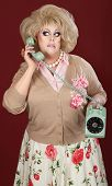 stock photo of cross-dresser  - Confused drag queen on phone call over maroon background - JPG