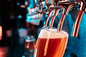 Bartender Pouring A Large Lager Beer In Tap. Bright And Modern Neon Light, Males Hands. Pouring Beer poster