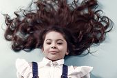Girl With Long Healthy Brunette Hair On Blue Background. Little Child With Curly Hairstyle, Curls. B poster