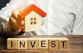 Wooden Blocks With The Word Invest And House In The Hands Of A Businessman. The Concept Of Investing poster