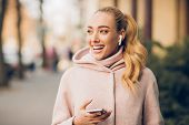 Stylish Woman Listening Music On Her Airpods, Walking In City At Autumn Day poster