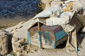 image of tarp  - Old boat with a tarp is placed upside down on the beach - JPG