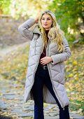 Puffer Fashion Trend Concept. Girl Fashionable Blonde Walk In Autumn Park. Woman Wear Warm Grey Jack poster