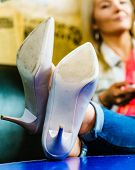Woman Relaxing Her Feet After Wearing White Heeled Elegant Shoes. Close Up Of High Heels. poster