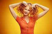 Happy laughing girl enjoys her beautiful red curly hair. Portrait over yellow background. Hair care, poster