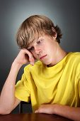 picture of teenage boys  - a teenaged boy sits looking depressed his head is resting on his hand - JPG