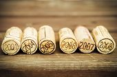 image of merlot  - Dated wine bottle corks on the wooden background - JPG