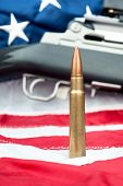 picture of assault-rifle  - A single bullet in front of an assault rifle sitting on an American flag - JPG