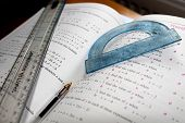 foto of protractor  - Mathematical Problem - Ruler, Protractor and Pen on Maths Book