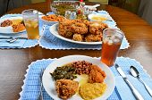 image of southern fried chicken  - Southern cooked soul food laid out on beautiful old oak dinner table - JPG