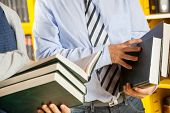 picture of librarian  - Midsection of male librarian and students holding books in college library - JPG